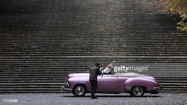 A newlywed couple poses for a photographer in a vintage car under stairs during their wedding photo session in Warsaw on 20 October 2007 AFP...