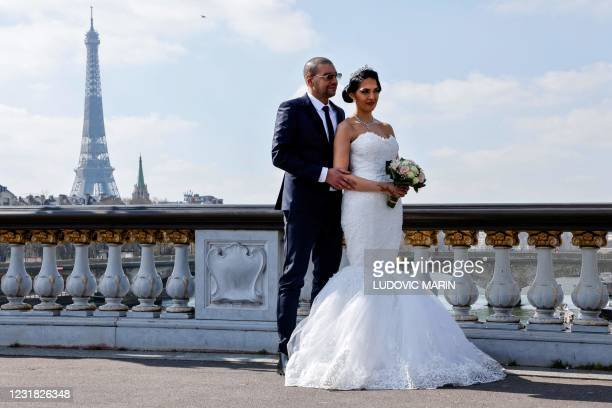 Newlywed couple poses for pictures on the Alexandre III bridge with the Eiffel tower in the background in Paris on March 20, 2021.