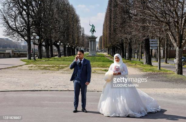 Newlywed couple poses for pictures with the monument to La Fayette in the background in Paris on March 20, 2021.