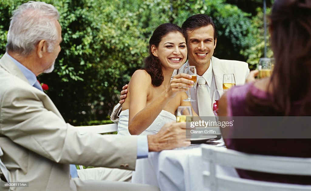 Newlywed Couple Raising A Toast At A Wedding Reception Stock Photo