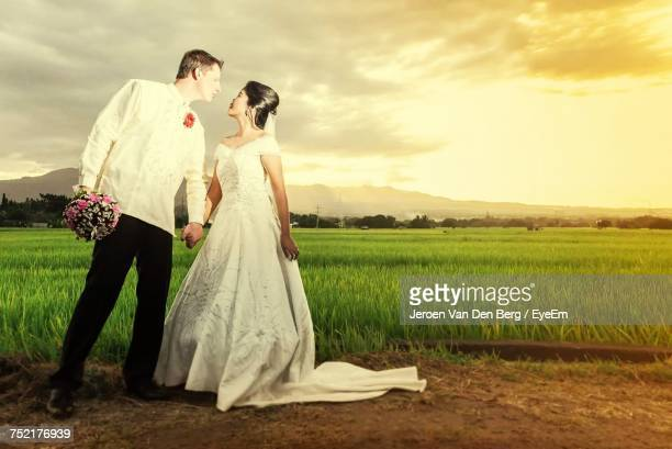 Newlywed Couple Romancing While Standing On Field Against Sky During Sunset