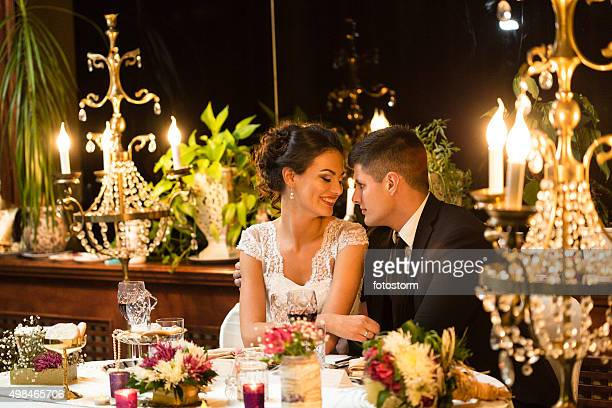 Newlywed couple sharing romantic moments at dinner