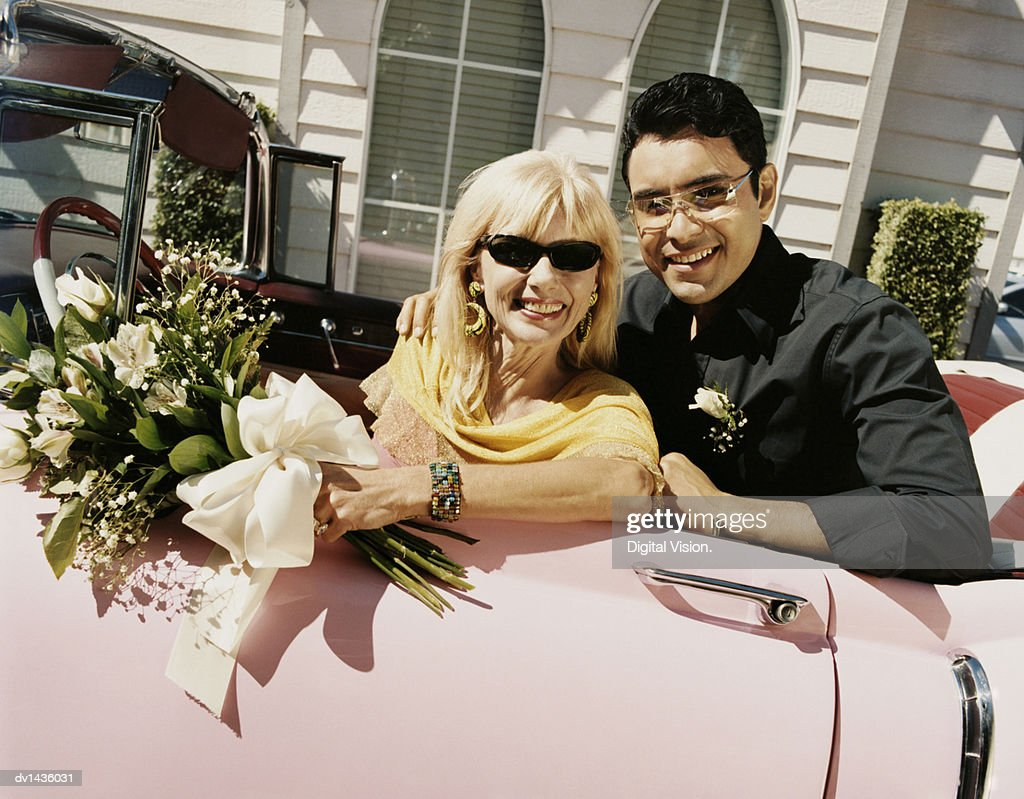 Newlywed Couple Sitting In A Pink 1950s Style Car Stock Photo