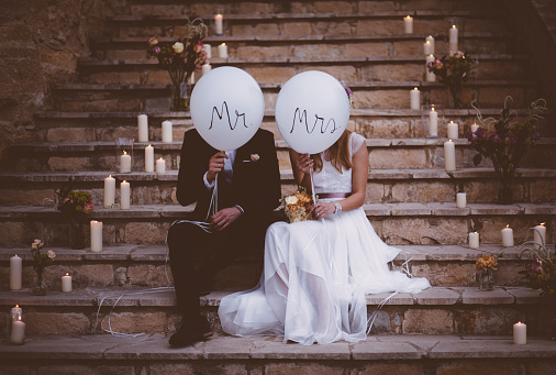 Newlywed couple sitting on steps and holding balloons 926606066