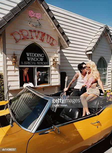 Newlywed Couple Sitting on the Backseat of a Convertible in Front of a Wedding Chapel and Groom Kissing Bride