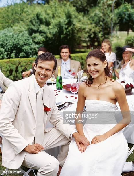 newlywed couple sitting together and holding hands
