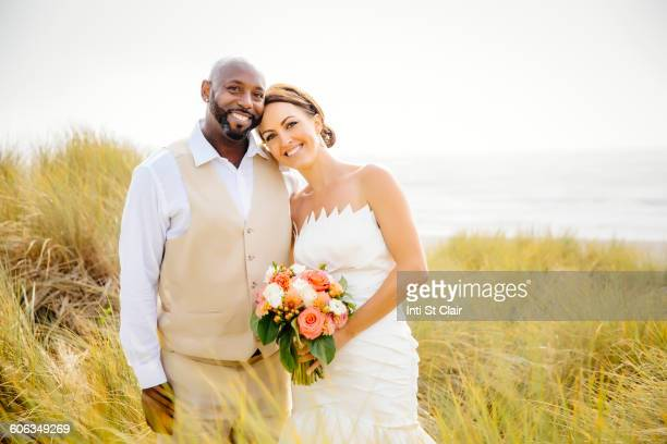 Newlywed couple smiling in grass