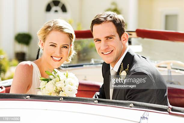 Newlywed Couple Smiling While Sitting In Car