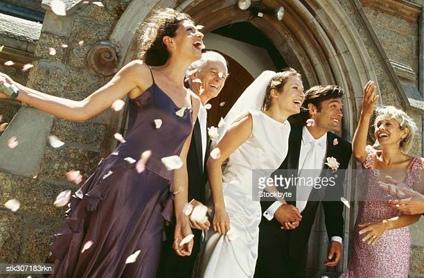 newlywed couple standing outside a church with their parents and guests - church wedding decorations stock pictures, royalty-free photos & images