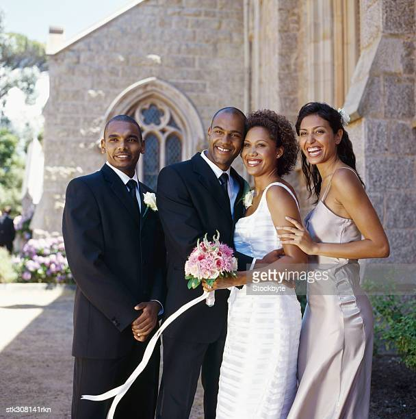 newlywed couple standing with a best man and a bridesmaid