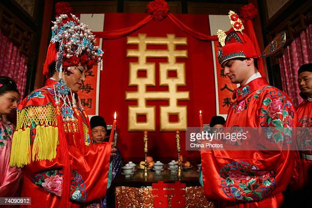 A newlywed couple the groom from France and bride from China attend their Chinese style wedding ceremony at the Grand Sight Garden on May 5 2007 in...