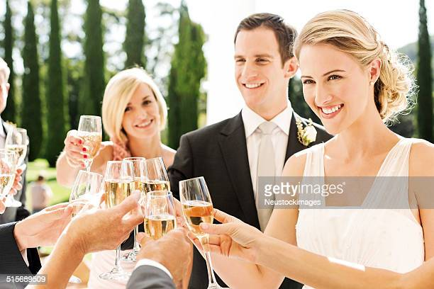 Newlywed Couple Toasting Champagne Flutes With Guests At Wedding