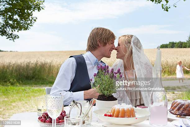 Newlywed couple touching noses outdoors