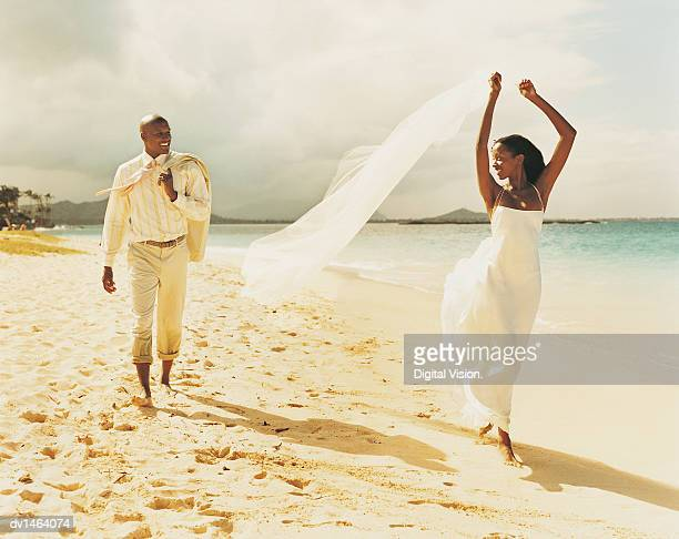 Newlywed Couple Walk Along a Beach, She Holding Veil Above Her Head