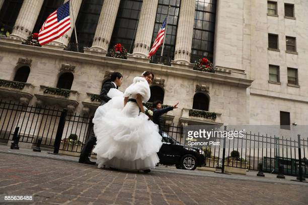 A newlywed couple walk in front of the New York Stock Exchange at the end of the trading day on December 4 2017 in New York City Banks and retailers...