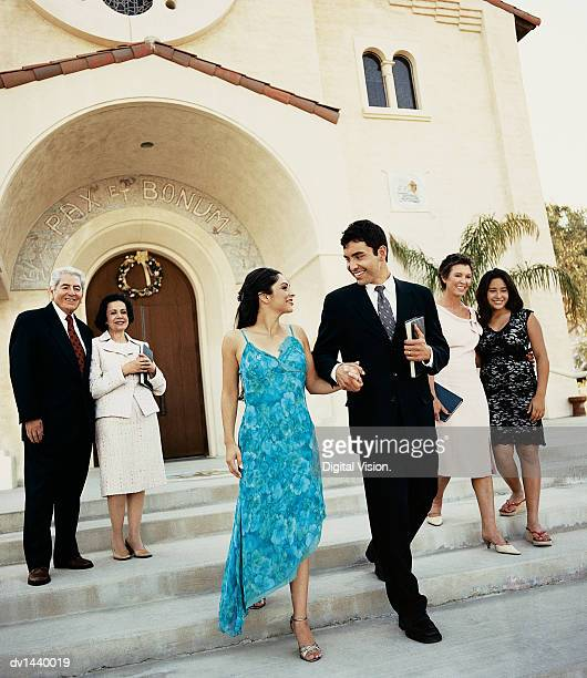 Newlywed Couple Walk Side by Side on the Steps Outside a Church, Their Parents and Relatives Behind Them