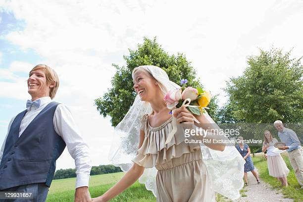 Newlywed couple walking hand-in-hand