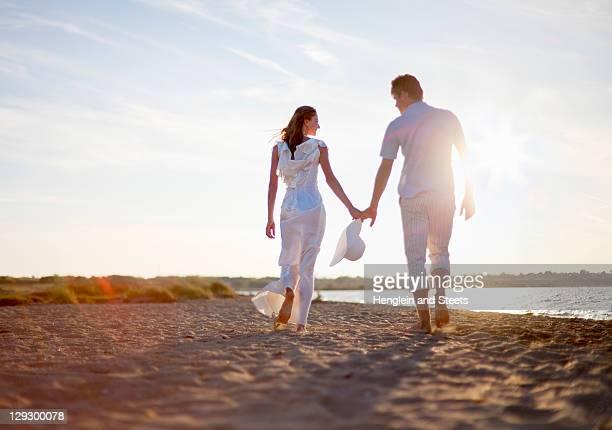 Newlywed couple walking on beach