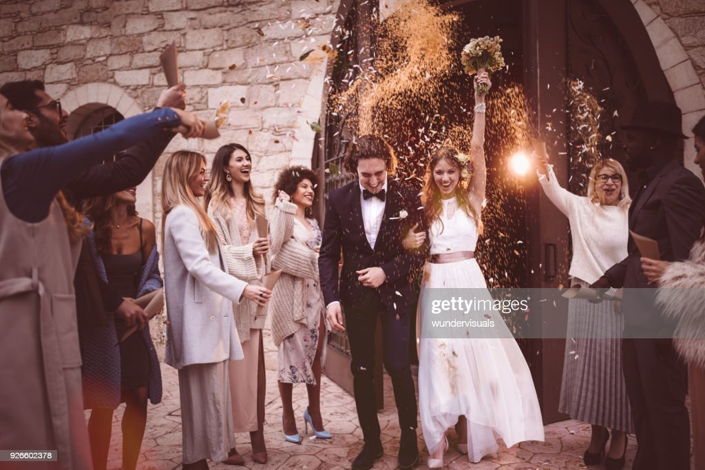 Newlywed couple walking out church and celebrating wedding with confetti : Stock Photo