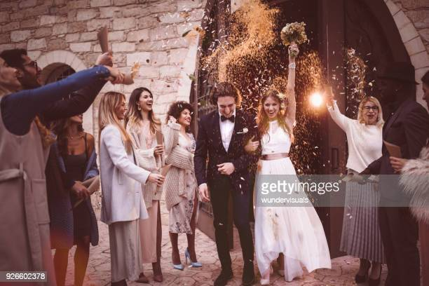 newlywed couple walking out church and celebrating wedding with confetti - matrimonio foto e immagini stock