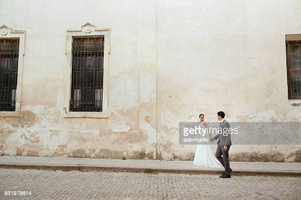 Newlywed couple walking the streets of Havana Cuba