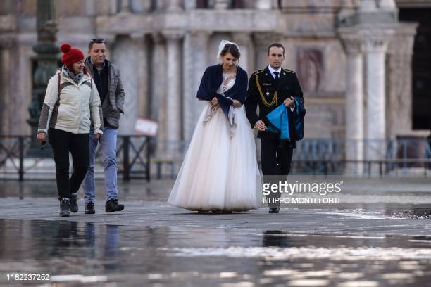 A newlywed couple walks across a flooded square on November 14 2019 in Venice Much of Venice was left under water after the highest tide in 50 years...