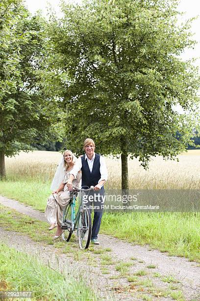Newlywed couple with bike on dirt path