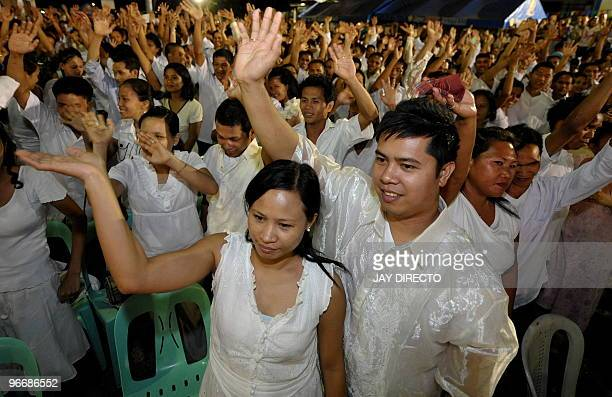 Newlywed couples wave after being pronounced husband and wife at a mass Valentine's Day wedding ceremony in Caloocan City suburb of Manila on...
