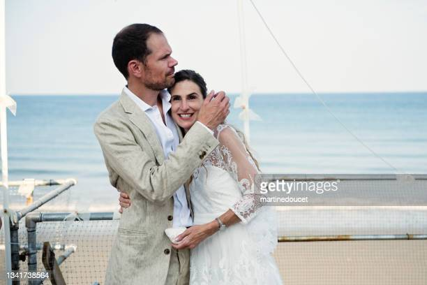 """newlywed embrace at small wedding ceremony in family beach house. - """"martine doucet"""" or martinedoucet stock pictures, royalty-free photos & images"""