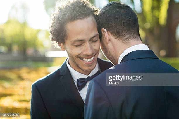 Newlywed gay couple embracing outdoors