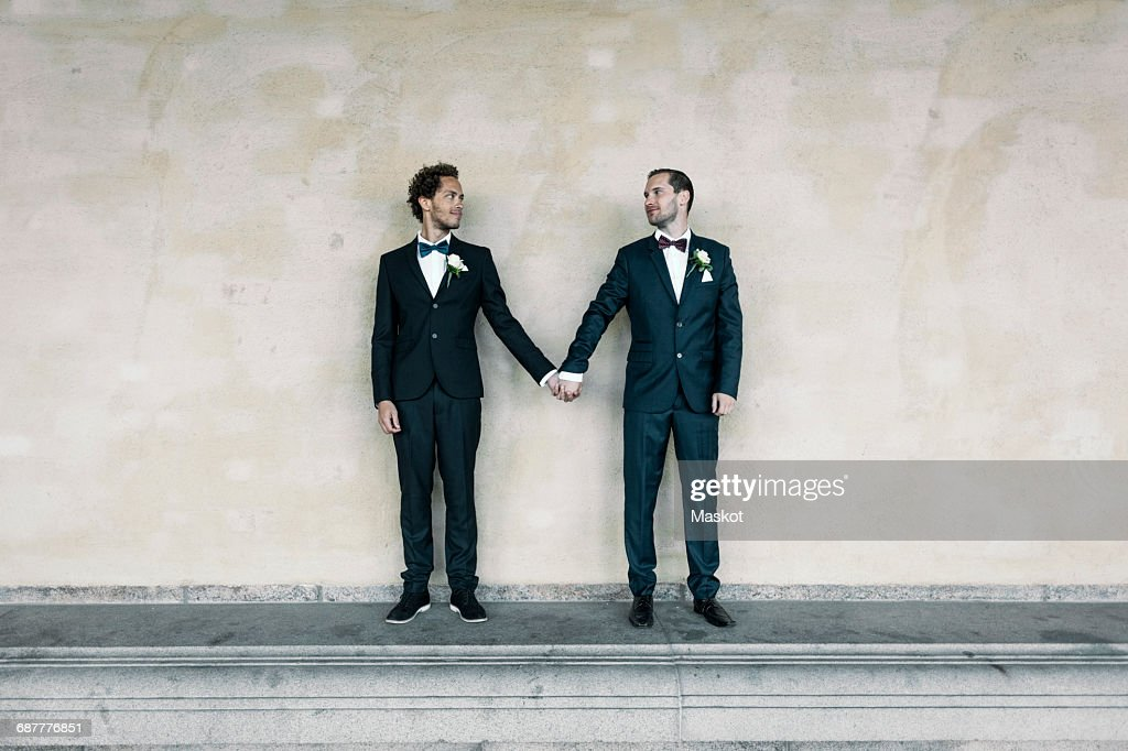 Newlywed gay couple standing while holding hands on bench against wall : ストックフォト