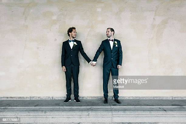 Newlywed gay couple standing while holding hands on bench against wall