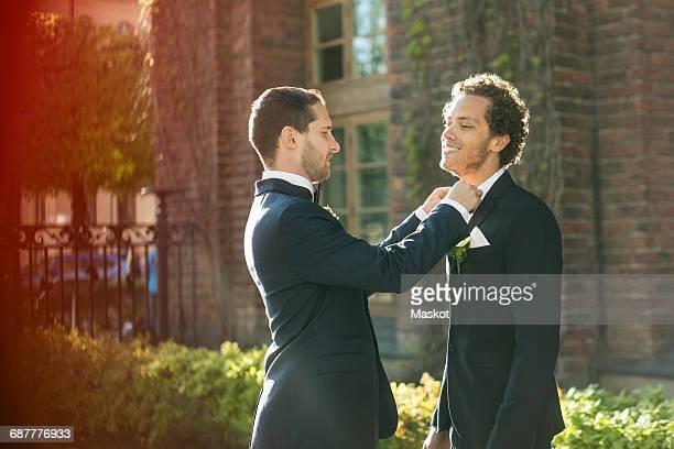 Newlywed gay man adjusting bow tie of partner