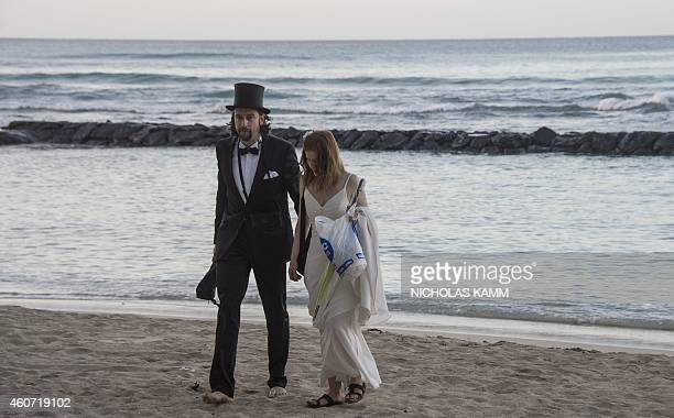 A newlywed German couple still wearing their wedding clothes eight days after the event walk on Waikiki beach in Honolulu on December 20 2014 as they...
