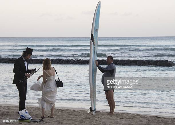 Newlywed German couple, still wearing their wedding clothes eight days after the event, gather their belongings on Waikiki beach in Honolulu on...