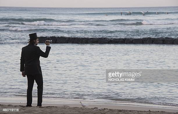 Newlywed German man, still wearing his wedding clothes eight days after the event, films surfers on Waikiki beach in Honolulu on December 20, 2014 as...