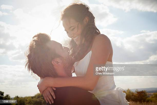 Newlywed groom holding bride outdoors