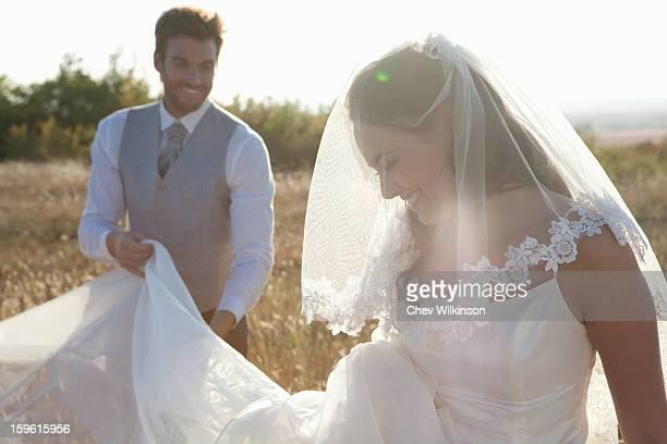 Newlywed groom holding brides dress