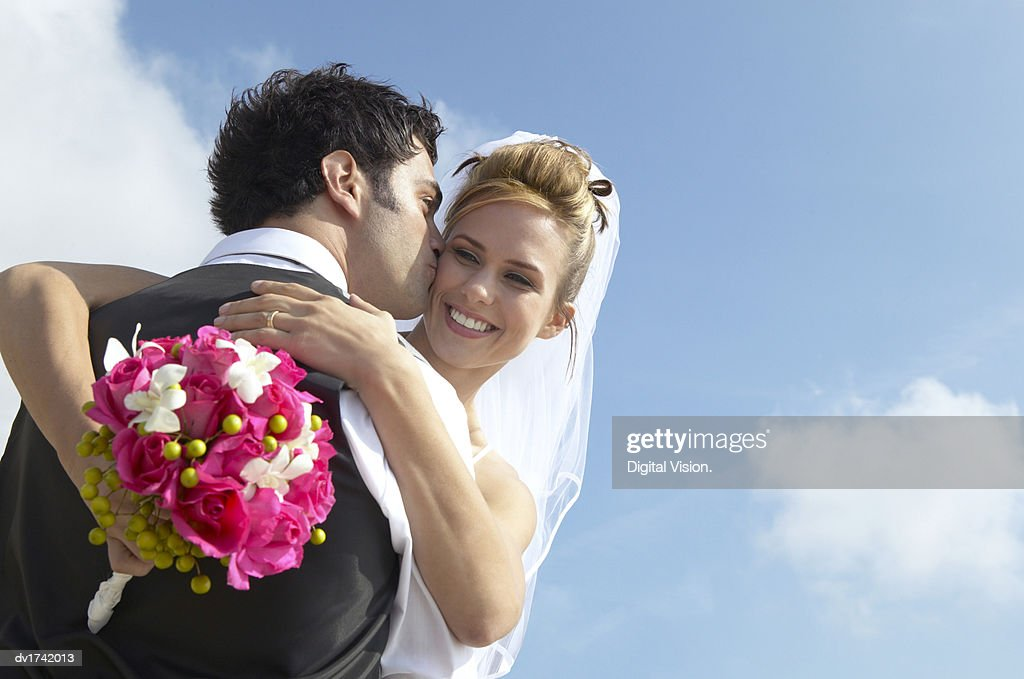 Newlywed Groom Kisses a Bride Holding a Bouquet on Her Cheek : Stock Photo