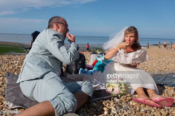 Newlywed groom Paul and bride Zoe have just been married at a nearby beach venue and continue their wedding ceremony by eating bags of chips on the...