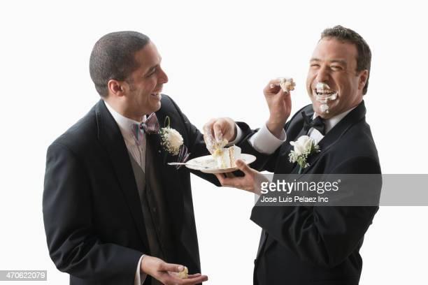Newlywed grooms eating cake