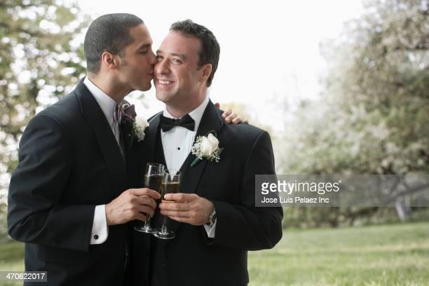 Newlywed grooms kissing