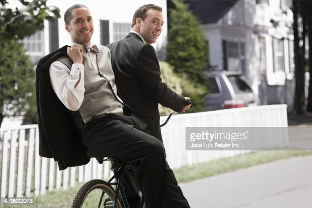 Newlywed grooms riding bicycle