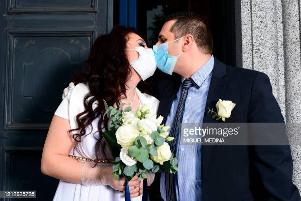Newly-wed Italians Ester Concilio and Rafaele Carbonelli kiss while wearing face masks following their wedding ceremony at the Briosco's town hall,...