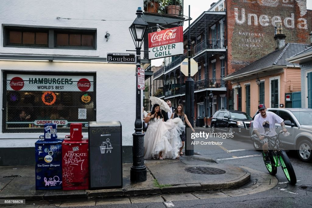 Newlywed Kaila Hager walks from her wedding ceremony to a bar in the French Quarter in New Orleans on October 7, 2017. US Gulf Coast residents scrambled with last-minute preparations Saturday as the outer bands of Hurricane Nate began lashing New Orleans amid fears it could intensify into a more powerful Category Two storm. Nate spawned widespread flooding and left dozens of people dead in Central America, the latest in a series of deadly storms to hammer Caribbean islands, Mexico and the southeastern US in this exceptionally busy hurricane season. / AFP PHOTO / Bryan Tarnowski