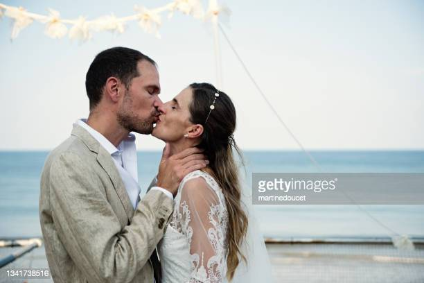 """newlywed kissing at small wedding ceremony in family beach house. - """"martine doucet"""" or martinedoucet stock pictures, royalty-free photos & images"""