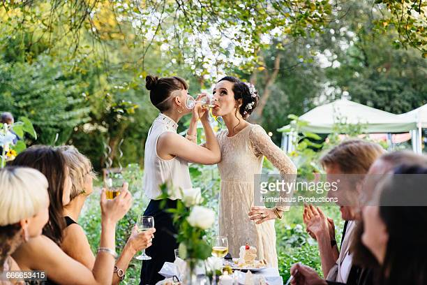 newlywed lesbian couple drinking - wedding reception stock pictures, royalty-free photos & images