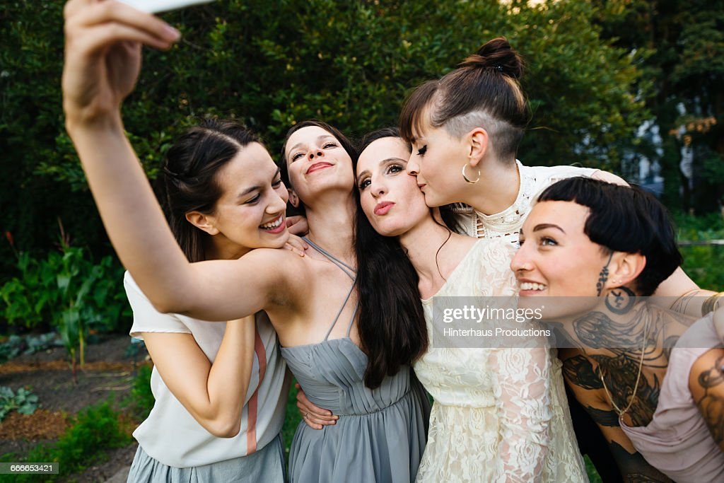 Newlywed lesbian couple with friends doing selfie : Stock Photo