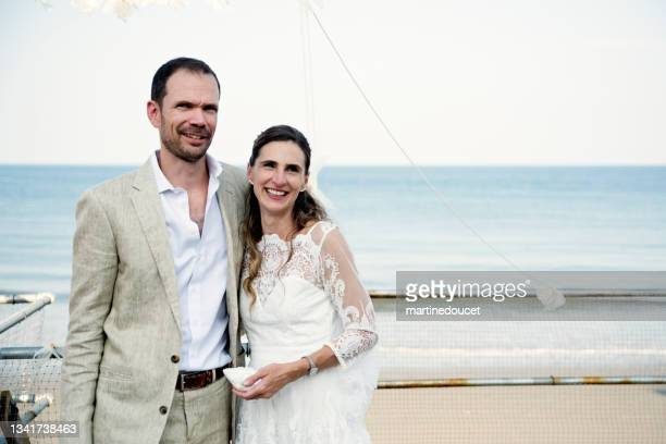 """newlywed portrait at small wedding ceremony in family beach house. - """"martine doucet"""" or martinedoucet stock pictures, royalty-free photos & images"""