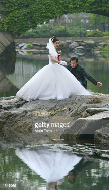 Newlywed Tina Moeing braves a drizzling rain as she is posed by photographer Chenjean Moeing in Central Park May 13 2002 in New York City A storm...